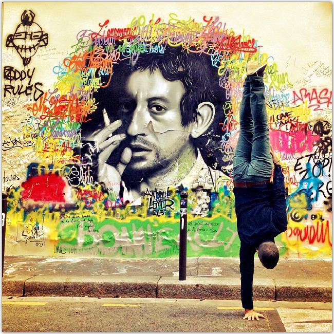 ストリートアートの前で逆立ちする男性